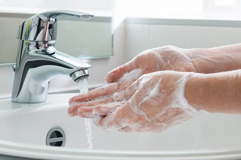 soapy hands by running water faucet