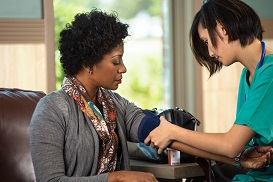 Nursing taking patient's blood pressure
