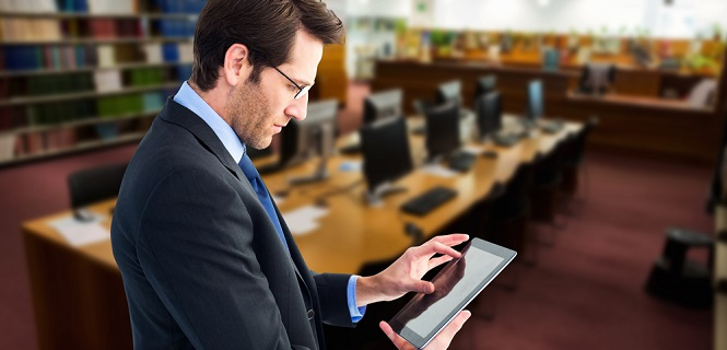 man looking at tablet in library