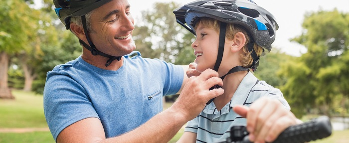 father and son wearing biking helmets