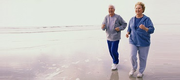 portrait of senior couple jogging on the beach