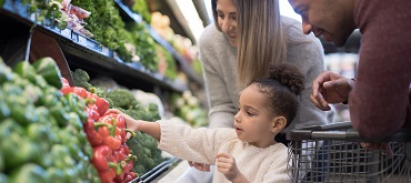 parents and daughter picking out vegetables at grocery store