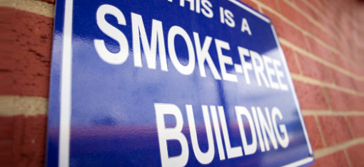 This is a smoke free building sign posted on brick wall.