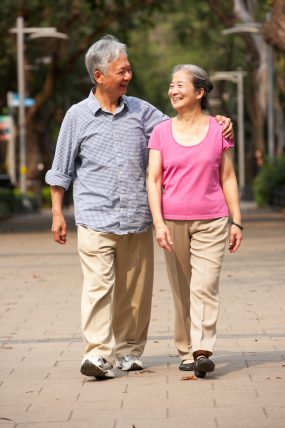 smiling older couple walking outside together