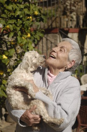 older woman laughing with her dog
