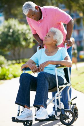 older man pushing an older woman in a wheelchair outside