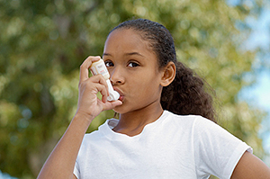 Girl (7-9) using inhaler, outdoors - Air Pollution
