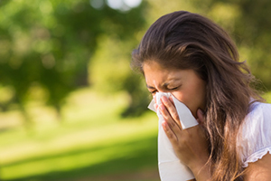 Woman blowing nose with tissue - Allergy