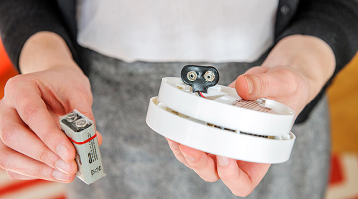 a battery in one hand, and a CO detector in the other