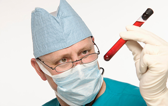 man in lab mask holding a test tube
