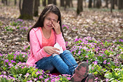 girl with itchy eyes sitting among flowers