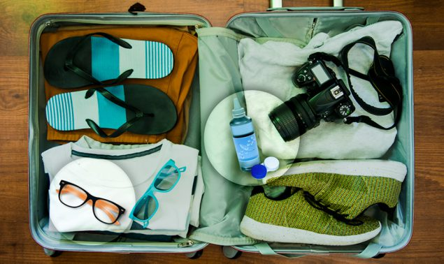 Open suitcase with clothing items and a contact lens travel kit