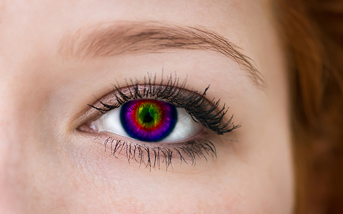 Close up image of a woman's eye with a multicolored contact lens.