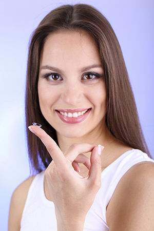 woman holding contact lens on a fingertip smiling