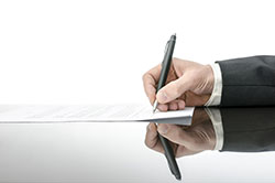 Person signing contract with pen.