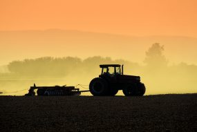 Silhouetted tractor farming at daybreak.