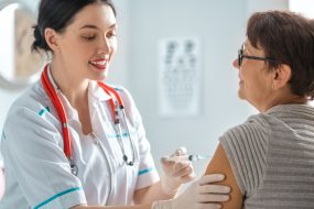 Mature woman receiving a vaccination shot in arm from young, female healthcare provider.
