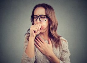 Woman coughing, covering her mouth and holding her chest.
