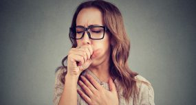 Photo of a woman coughing, covering her mouth with her fist and holding her chest.