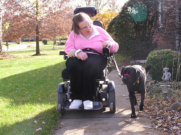 전동 휠체어를 타고 개를 산책시키는 여성