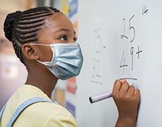 Estudiante de escuela primaria con mascarilla resuelve un problema de matemáticas en el pizarrón