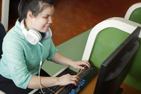 점자를 읽으며 컴퓨터를 사용 중인 소녀