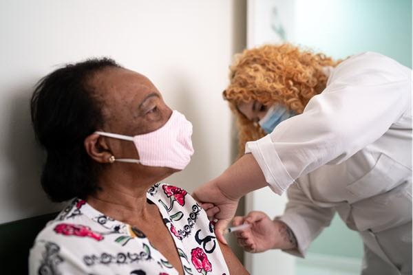 의료진으로부터 백신을 맞고 있는 노인 여성