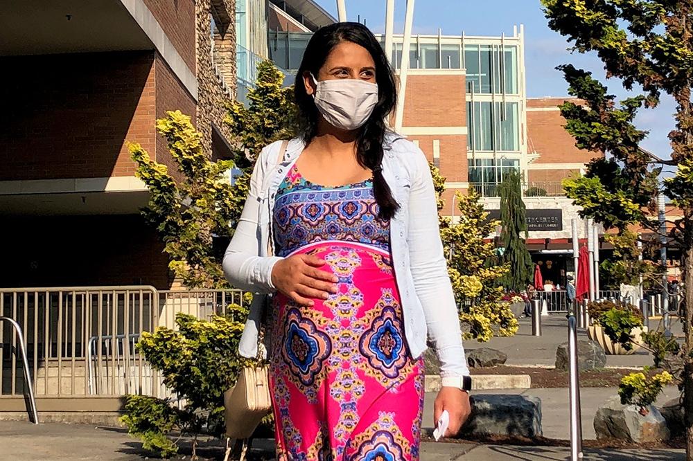 Phụ nữ mang thai đang đi bộ trong thành phố có đeo khẩu trang bảo vệ bằng vải