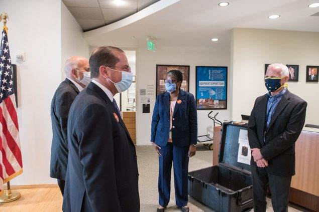 The photo shows four people in a CDC reception area wearing masks and looking at each other. Leandris Liburd, in the middle, is CDC's chief health equity officer. She is seen here with - from left to right - CDC director Dr. Robert Redfield, Alex Azar, Secretary of Health and Human Services, and Dr. Jay Butler, CDC's deputy director for infectious diseases.