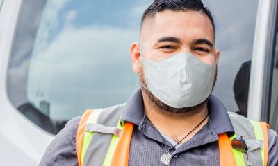 trabajador de entrega con mascarilla y chaleco de seguridad