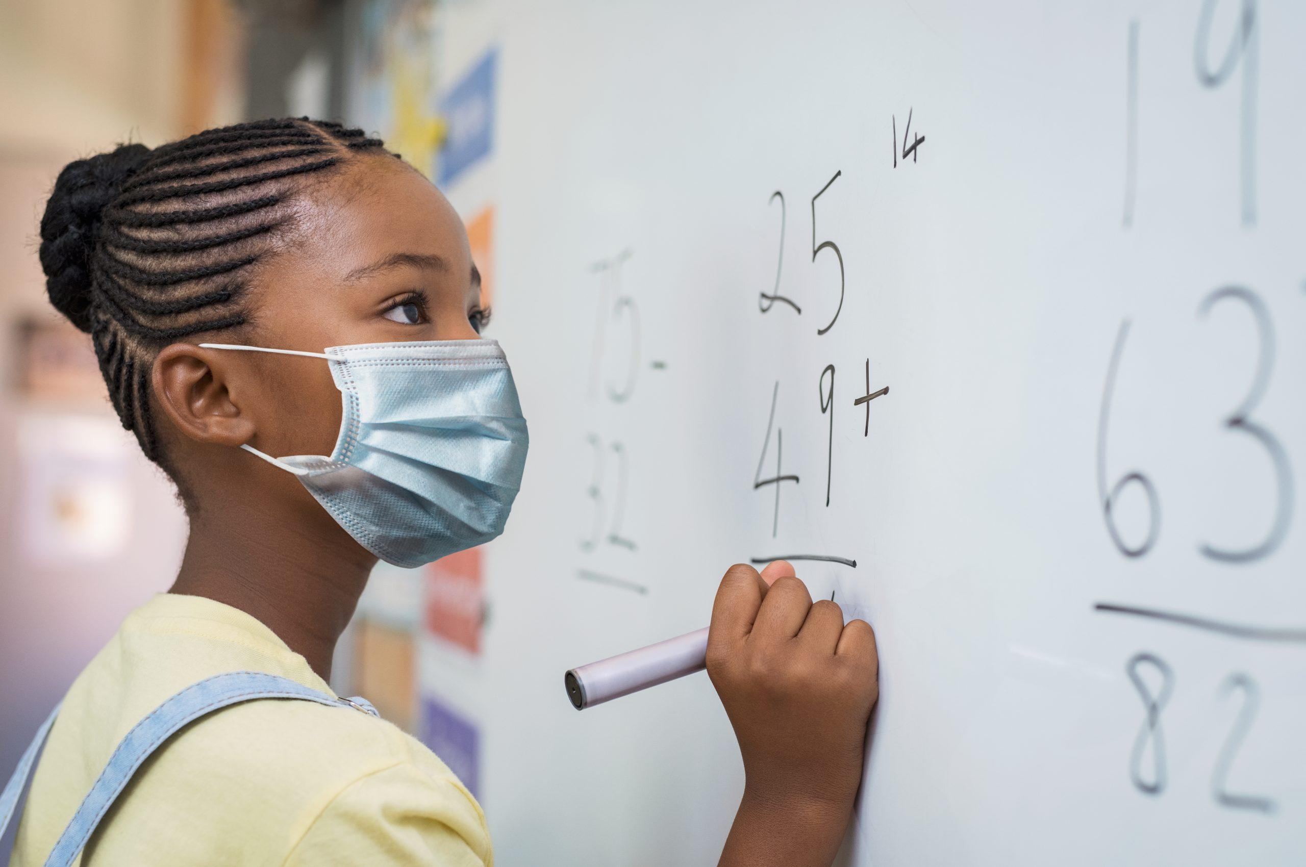 마스크를 착용하고 화이트보드에 필기 중인 여학생