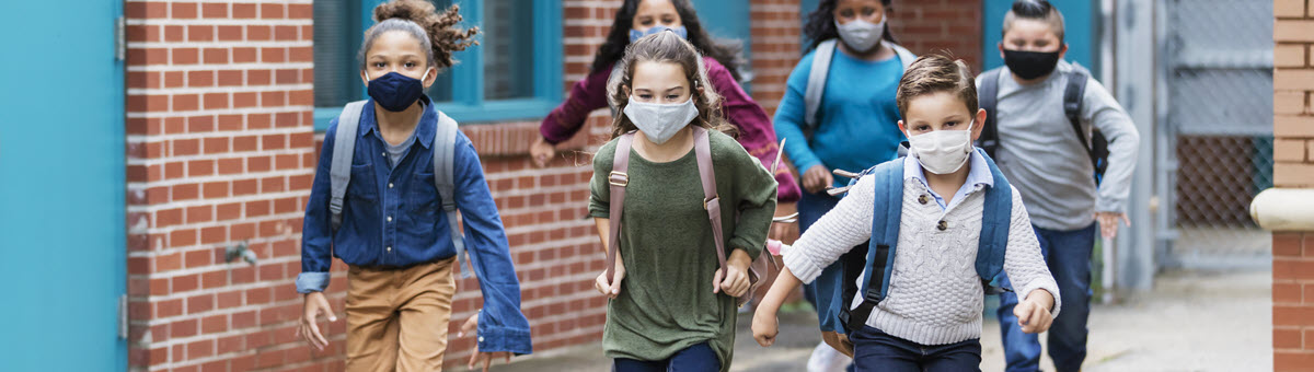 kids wearing masks running outside a school building