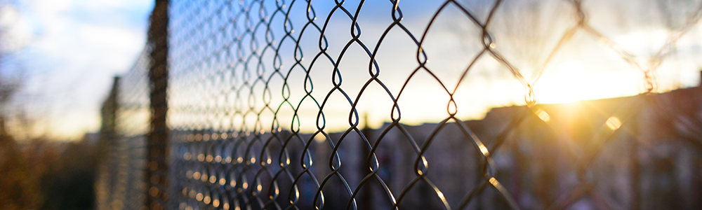 Imagen de una cerca de alambre con una prisión en el fondo