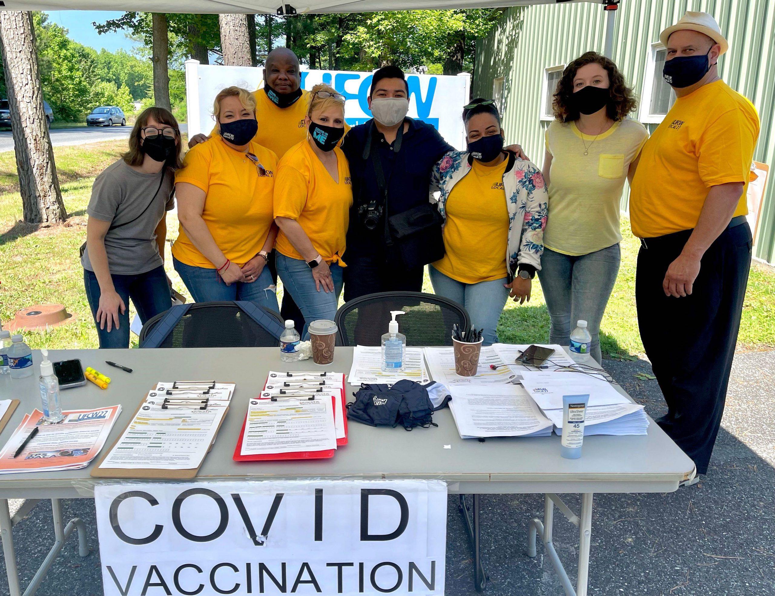 마스크를 쓰고 COVID 백신 접종소 테이블 뒤에 서 있는 성인 그룹