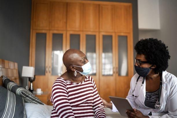 黑人医生和患者,戴着口罩交流
