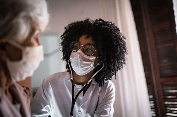 护士戴着口罩与患者交谈