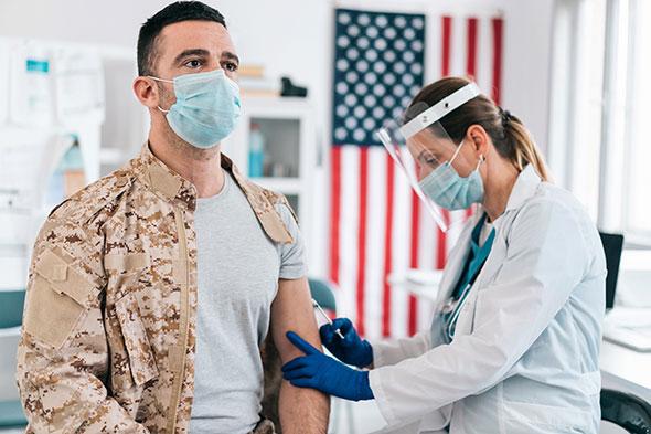 医生穿戴防护服给士兵注射COVID-19疫苗