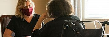 người phụ nữ nói chuyện với người phụ nữ lớn tuổi hơn đeo mặt nạ