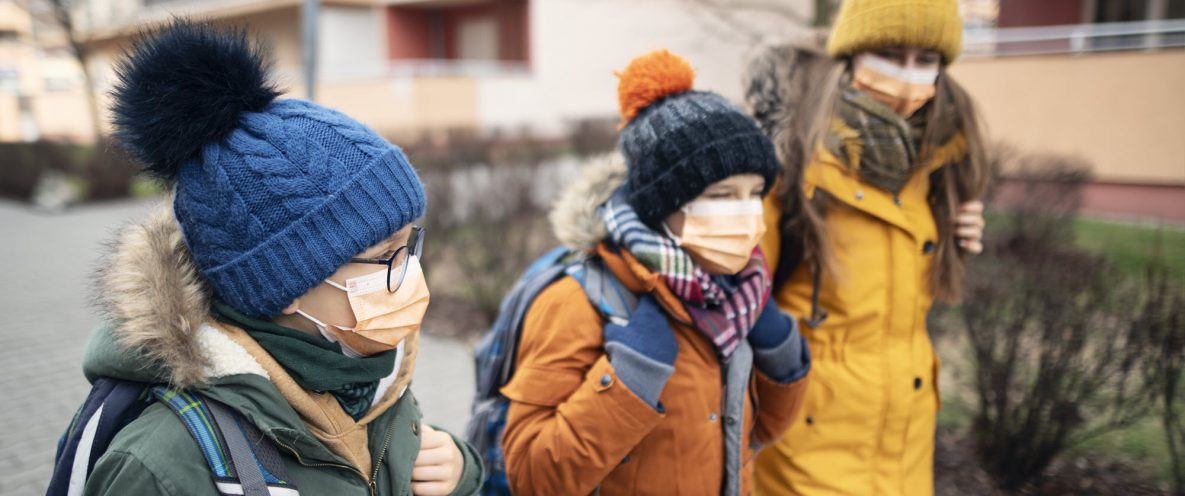 3 kids walking to school in winter