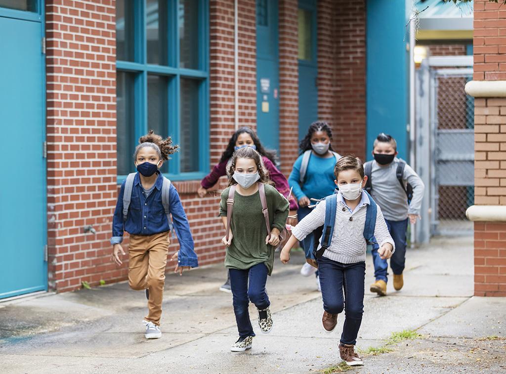 6 trẻ đeo khẩu trang và đeo balo chạy trong sân trường