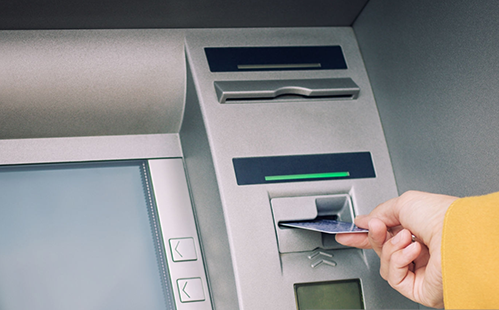 A hand inserting a debit or credit card into ATM machine