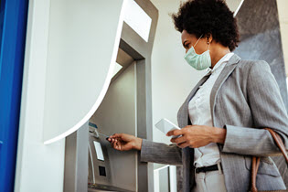 Woman inserting a debit or credit card into ATM machine