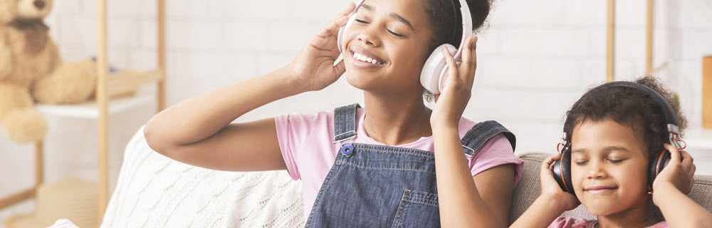 two young girls listening to music on headphones