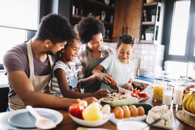 Gia đình Mỹ gốc Phi vui vẻ cùng nhau chuẩn bị đồ ăn tốt cho sức khỏe trong bếp