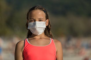 a young girl in a swimsuit wearing a cloth face cover on a beach