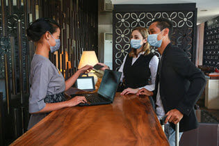 man and woman in mask checking into a hotel