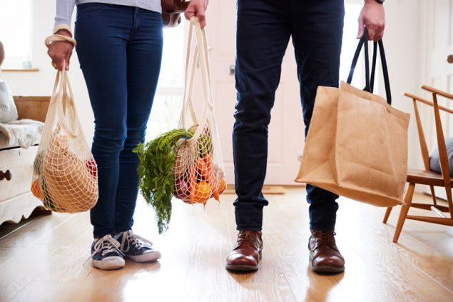 Ảnh cận cảnh cặp đôi trở về nhà từ chuyến đi mua sắm mang theo đồ tạp hóa trong các túi nhựa miễn phí