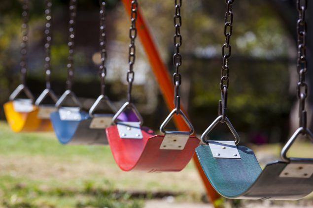 Close up of empty colorful swings at a playground