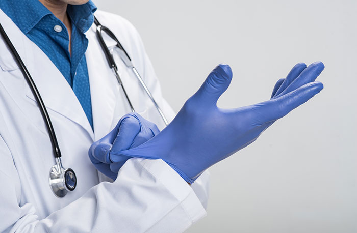 Male physician wearing blue gloves.