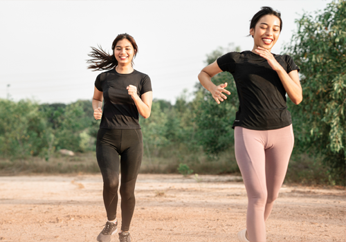 Two women jogging on a trail